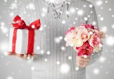 供以人员拿着花和礼物盒花束  免版税库存照片