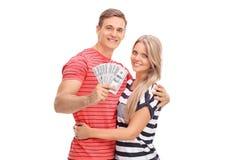 供以人员拿着金钱和摆在与他的女朋友 免版税库存图片