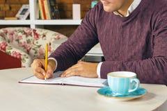 供以人员拿着铅笔和写在纸在日志 库存图片