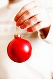 供以人员拿着从手指的一个红色圣诞树球 免版税库存照片