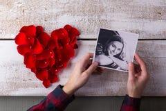 供以人员拿着他的女朋友照片的手 重点瓣红色上升了 库存图片