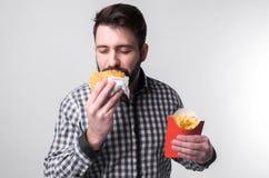 供以人员拿着amburger和炸薯条片断  学生吃快餐 没有用的食物 非常饥饿的人 库存图片