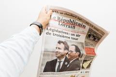 供以人员拿着le republicain与伊曼纽尔宏指令的lorrain报纸 免版税库存照片