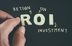 供以人员指向在黑皮革背景写的词ROI回收投资的手 图库摄影