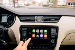 供以人员按在苹果计算机CarPlay主要屏幕上的家庭按钮 免版税库存照片