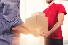 供以人员接受箱子交付从送货业务传讯者的 库存照片