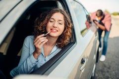 供以人员推挤一辆残破的汽车,妇女司机 图库摄影