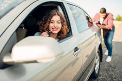 供以人员推挤一辆残破的汽车,妇女司机 库存照片