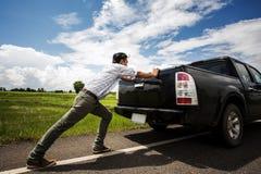 供以人员推挤在路下的一辆残破的汽车 免版税图库摄影