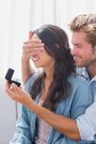 供以人员掩藏的妻子眼睛提供她定婚戒指 库存照片