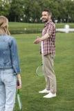 供以人员提供援助手对妇女,当打羽毛球时 免版税库存图片