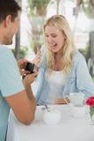 供以人员提出婚姻给他的震惊白肤金发的女朋友 免版税库存图片