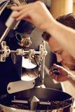 供以人员操作一个现代咖啡烧烤机器和嗅到 免版税库存照片