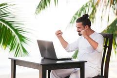 供以人员放松在与膝上型计算机,自由职业者工作场所,梦想工作的海滩 免版税库存照片