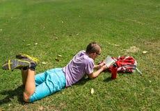供以人员放置在草和读他的笔记 免版税库存图片
