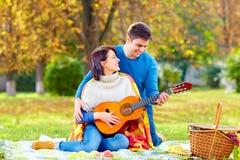 供以人员教的女孩戏剧在秋天野餐的一把吉他 免版税库存照片