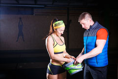 供以人员教练员和妇女健身房帮助用滑石,镁润滑手 免版税图库摄影