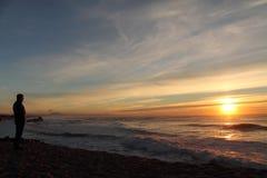 供以人员敬佩有碎波的剪影大西洋与山在后面的la rhune在日落, capbreton,法国 免版税库存图片