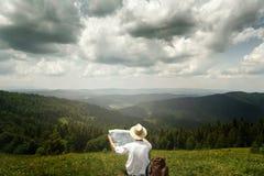 供以人员旅客探索的地图和在晴朗的小山顶部坐b 库存图片