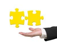 供以人员显示两个3D金子七巧板片断的手 免版税库存照片