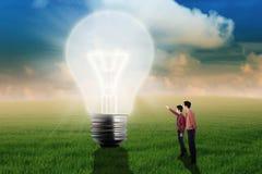 供以人员显示大电灯泡给他的经理 免版税库存图片