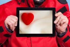 供以人员显示心脏在片剂触感衰减器的爱标志 免版税库存图片