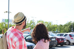 供以人员显示某事给在城市街道上的妇女反对清楚的天空 免版税库存照片