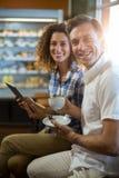 供以人员有使用数字式片剂的茶和妇女在超级市场 免版税库存照片
