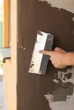供以人员有涂灰泥房子墙壁的修平刀的手 免版税库存照片