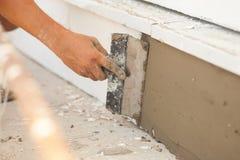 供以人员有涂灰泥房子的基础的修平刀的手 库存图片