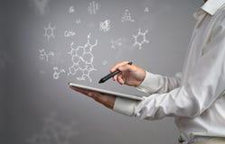 供以人员有片剂个人计算机和铁笔的科学家或者笔与在灰色背景的化学式一起使用 免版税库存图片