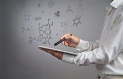 供以人员有片剂个人计算机和铁笔的科学家或者笔与在灰色背景的化学式一起使用 免版税库存照片