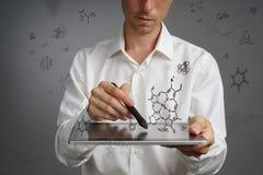 供以人员有片剂个人计算机和铁笔的科学家或者笔与在灰色背景的化学式一起使用 图库摄影
