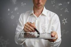 供以人员有片剂个人计算机和铁笔的科学家或者笔与在灰色背景的化学式一起使用 免版税图库摄影