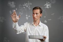 供以人员有片剂个人计算机的科学家与在灰色背景的化学式一起使用 免版税图库摄影