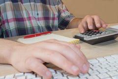供以人员有铅笔、笔记本和计算器的手在木桌上 人在办公室屋子使用在桌上的一个计算器 免版税库存图片