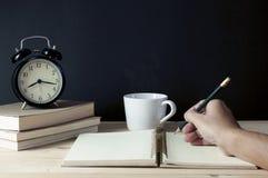 供以人员有铅笔文字的手在与咖啡的笔记薄 库存图片