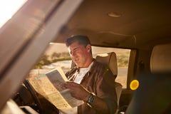 供以人员检查在一张地图的方向在汽车 免版税图库摄影