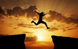 供以人员横跨从一个岩石的空白紧贴的跳跃对其他 库存图片