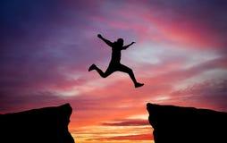 供以人员横跨从一个岩石的空白紧贴的跳跃对其他 免版税图库摄影