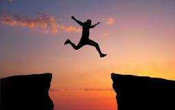 供以人员横跨从一个岩石的空白紧贴的跳跃对其他 免版税库存照片