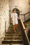供以人员步行沿着向下老石楼梯晴天 库存照片