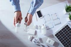供以人员比较一个白炽电灯泡和CFL灯 免版税库存图片