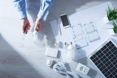 供以人员比较一个白炽电灯泡和CFL灯 免版税库存照片