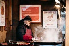 供以人员油煎土豆和香肠-一个传统圣诞节盘 免版税库存照片