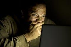 供以人员注视着后冲击在他的膝上型计算机夜 免版税库存图片