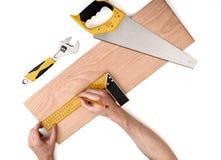 供以人员测量与铁统治者的手木板条,在白色背景 库存图片