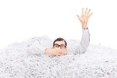 供以人员淹没在堆切细的纸 免版税库存图片