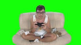 供以人员演奏与gamepad的游戏玩家计算机游戏坐肮脏的长沙发 股票录像