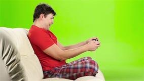 供以人员演奏与gamepad的计算机游戏坐长沙发 慢的行动 股票视频